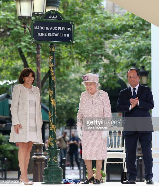 Anne Hidalgo Mayor of Paris and Francois Hollande President of France flank Queen Elizabeth II as she unveils a sign renaming Paris Flower Market on...