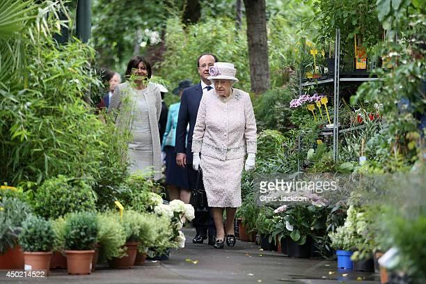 Anne Hidalgo Mayor of Paris and Francois Hollande President of France walk behind Queen Elizabeth II as she visits Paris Flower Market on June 7 2014...