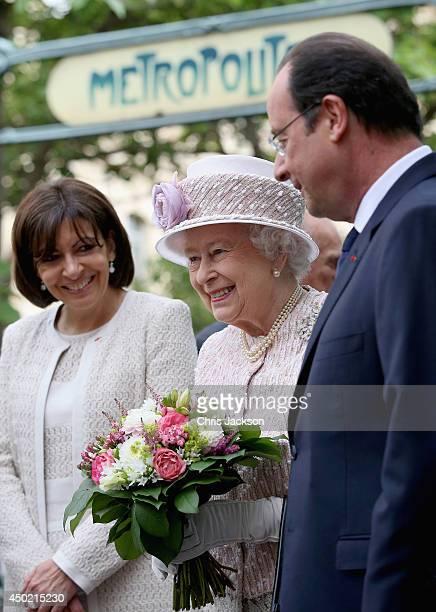 Anne Hidalgo Mayor of Paris and President of France Francois Hollande flank Queen Elizabeth II as she visits Paris Flower Market on June 7 2014 in...