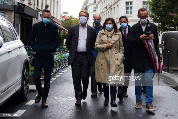 Anne Hidalgo, mayor of Paris, center, wears a protective face mask as she visits the scene of a reported a knife attack in Paris, France, on Friday,...