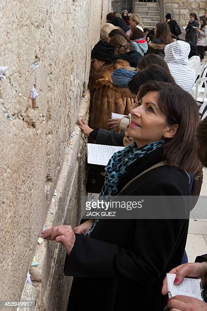 Anne Hidalgo Paris deputy mayor and Socialist Party candidate for the primary round of Paris municipal elections puts a paper with wishes in a crack...