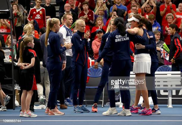 Anne Keothavong Great Britain Captain helps Johanna Konta of Great Britain back to her chair to celebrate with her teammates after victory in her...
