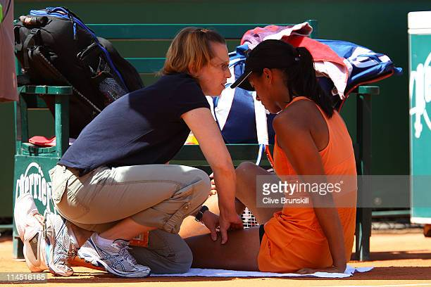 Anne Keothavong of Great Britain receives treatment for an injury during the women's singles round one match between Anne Keothavong of Great Britain...