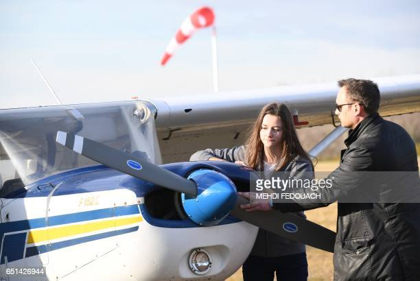 Anne Labbe France's youngest private airplane pilot checks a Cessna 152 plane with her instructor Emmanuel Deporte during a preflight review on March...