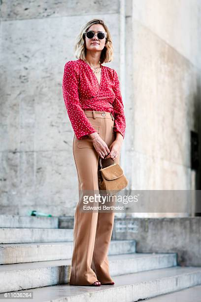 Anne Laure Mais is wearing brown trousers brown shoes a brown bag and a red shirt outside the Rochas show at the Palais de Tokyo during Paris Fashion...