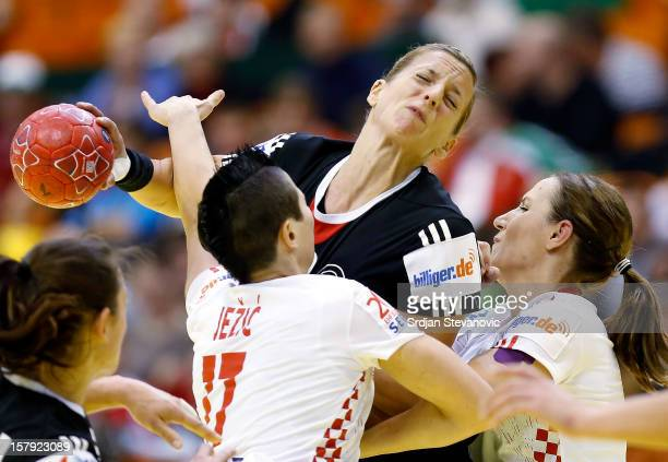 Anne Loerper of Germany is challenged by Katarina Jezic of Croatia during the Women's European Handball Championship 2012 Group C match between...