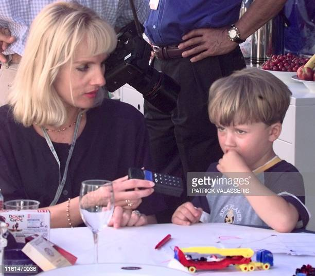 Anne Panis the wife of ProstPeugeot driver Olivier Panis hands a mobile phone to their son Aurelien 24 May some hours before the start of the 56th...
