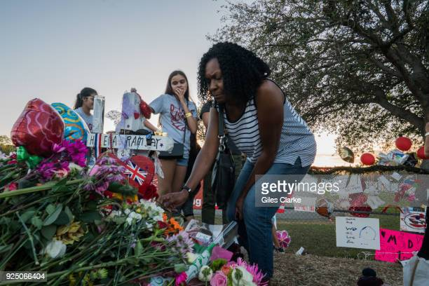 Anne Ramsey places a rose on her daughters' memorial site outside the Marjory Stoneman Douglas High School Anne moved from the UK to Florida in 1996...
