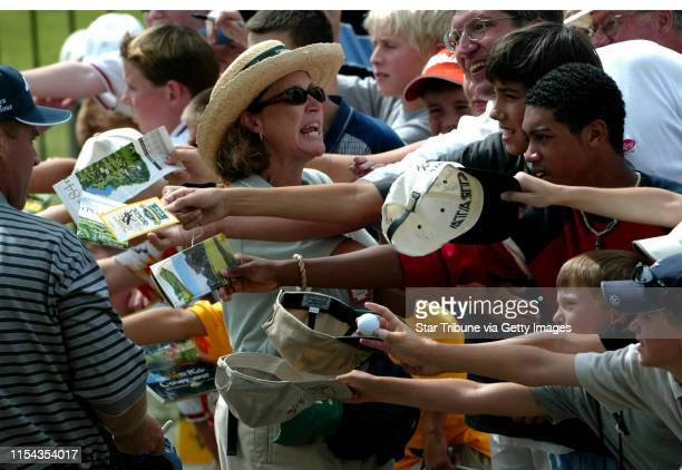Anne Scheuer, Eden Prairie, a volunteer at the PGA Championship, holds back the fans as they attempt to get autographs from the players to assure...