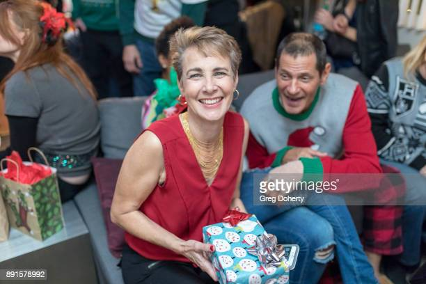 Anne Schoettle and Thomas Collabro display their Secret Santa Gifts at The Bay Ugly Sweater And Secret Santa Christmas Party at Private Residence on...