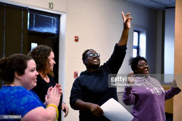 Anne Smith center and Iyanna Hutcherson right react after learning her team won the cooking challenge at the PHILLIPS school while teacherintern...
