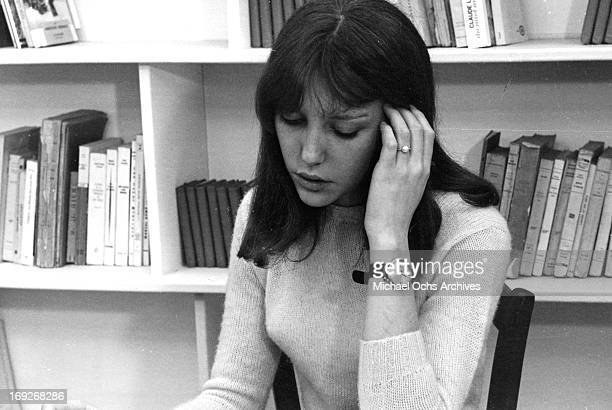 Anne Wiazemsky sitting in front of bookshelf in classroom in scene from the film 'La Chinoise' 1967
