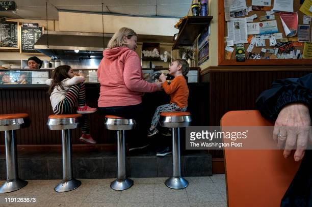 Anne Wilson center dines with her kids Bryony Ferguson and Henry Ferguson at Olympia Cafe in Martin's Additions MD on December 31 2019