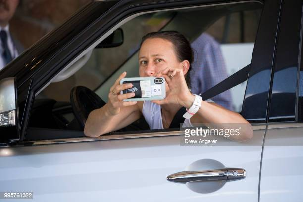 Anne Wojcicki cofounder and chief executive officer of 23andMe takes a photo of members of the media as she arrives at the Sun Valley Resort for the...