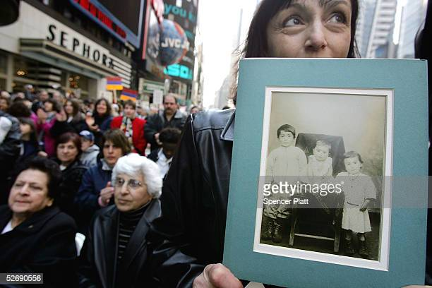 Anne Zartarian holds up a picture of her father sitting in Armenia with his two siblings that were subsequently killed during a rally in Times Square...