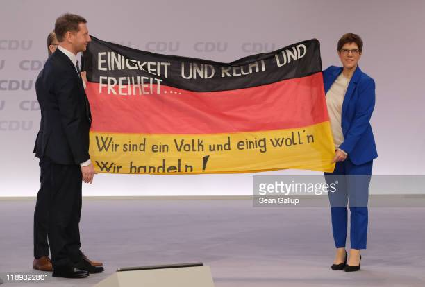 Annegret Kramp-Karrenbauer, leader of the German Christian Democrats receives a German flag with slogans from the East German 1989 revolution as...