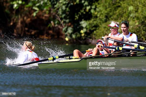 Annekatrin Thiele jumps into the water as Carina Baer Julia Lier and Lisa Schmidla of Germany react after winning Women's Scull Final A on Day 6 of...