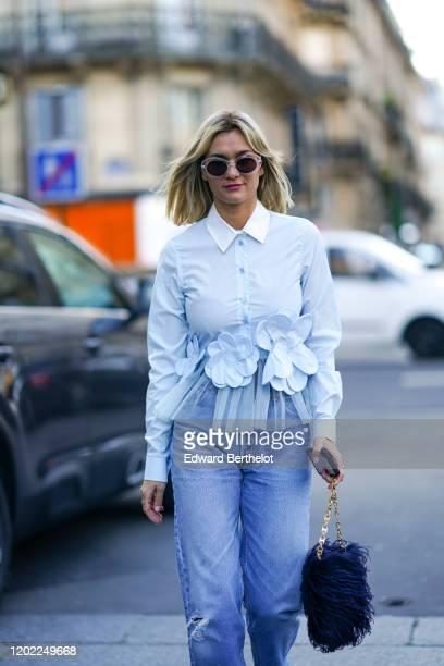 AnneLaure Mais wears sunglasses a light blue ruffled shirt with a white collar and flowers embroidered blue ripped jeans a bag decorated with...