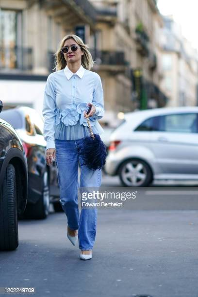 Anne-Laure Mais wears sunglasses, a light blue ruffled shirt with a white collar and flowers embroidered, blue ripped jeans, light blue pointy pumps,...