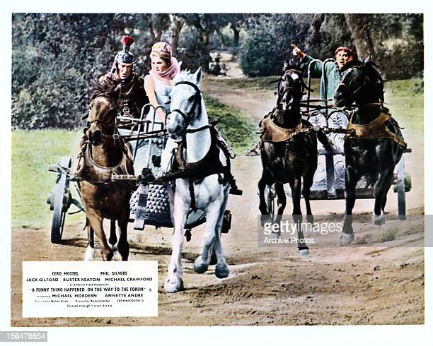 Annette Andre and Zero Mostel ride in chariots in a scene from the film 'A Funny Thing Happened On The Way To The Forum' 1966