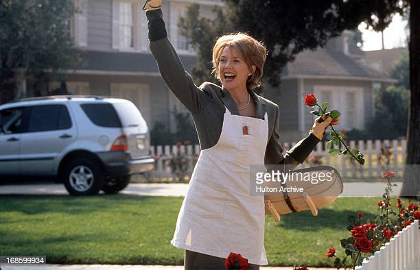 Annette Bening standing in a yard waiving with one hand and holding a rose in the other in a scene from the film 'American Beauty' 1999