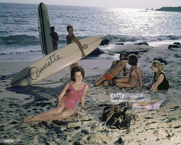 Annette Funicello US actress and singer wearing a pink swimsuit with white spots laying on the beach with three men and two women in the background...