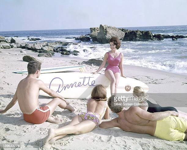 Annette Funicello US actress and singer wearing a pink swimsuit with white spots sitting on a surfboard on which is written 'Annette' looking at two...