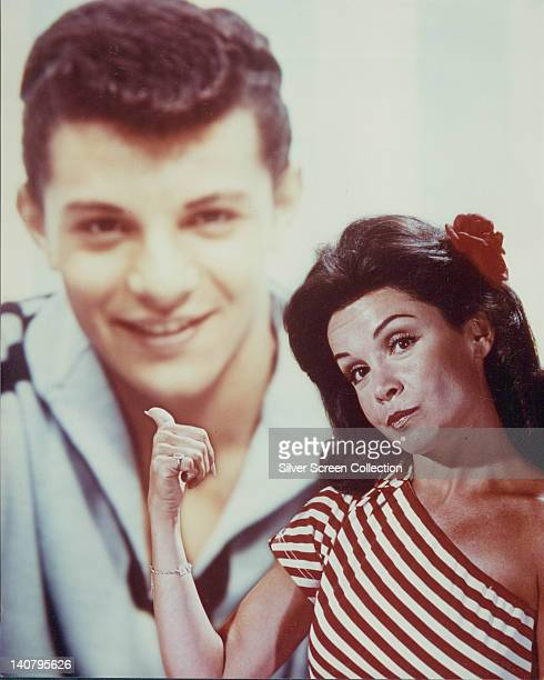 Annette Funicello US actress and singer wearing a red and white striped offtheshoulder top pointing with her thumb at a portrait behind her of...