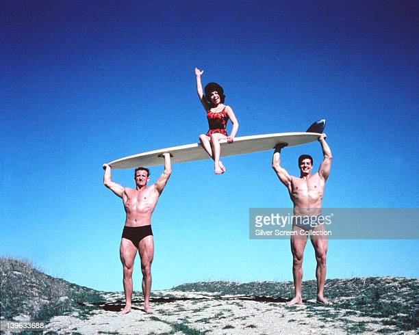 Annette Funicello US actress and singer wearing a red swimsuit and waving while sitting on a surfboard which is being carried by two men in a...