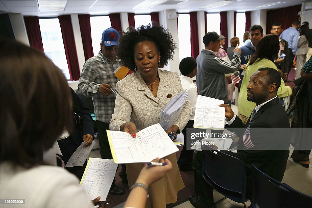 Annette Harewood from the New York City Commission on Human Rights collects completed voter registration forms from New American citizens following a naturalization ceremony held at the U.S. Citizenship and Immigration Services (USCIS), office on May 17, 2013 in New York City. One hundred and fifty immigrants from 38 different countries became U.S. citizens at the event. Some 11 million undocumented immigrants living in the U.S. stand to eventually gain American citizenship if Congress passes immigration reforms currently being negotiated.