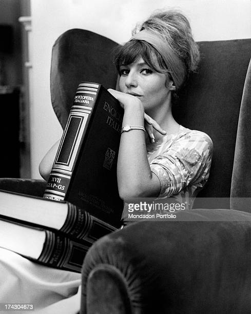 Annette Susanne Str¯yberg The Danish actress wife of the famous director Roger Vadim poses in the living room of her Roman house she holds a volume...