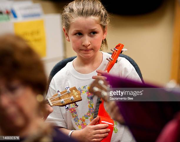 Annie Brown of Folsom California looks a little unsure of herself as she participates in the free Ukulele Club at The Nicholson Music Co in Folsom on...