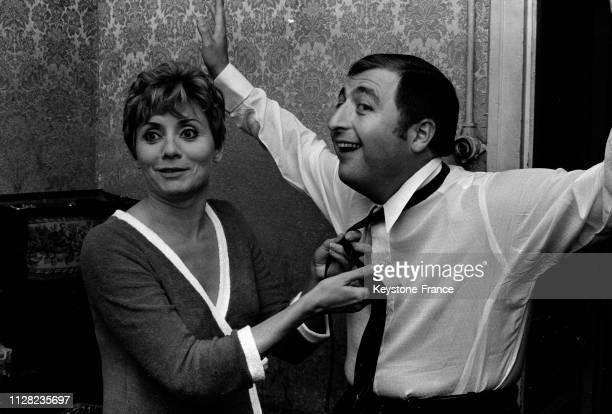Annie Cordy fait le noeud de cravate d'Henri Tisot dans les loges à Paris France en septembre 1968
