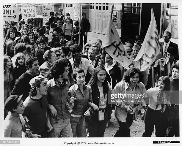 Annie Girardot and Bruno Pradal lead students in a march in a scene from the MGM movie 'To Die of Love' aka 'Mourir d'aimer' Circa 1972