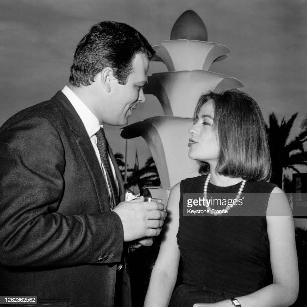 Annie Girardot et son mari Renato Salvatori photographiés discutant sur la Croisette à Cannes, France le 6 mai 1964.