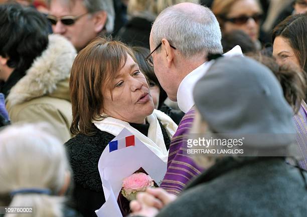 Annie Girardot's daughter Giulia Salvatori kisses French priest Philippe Desgens in front of the Paris Saint-Roch church after attending French...
