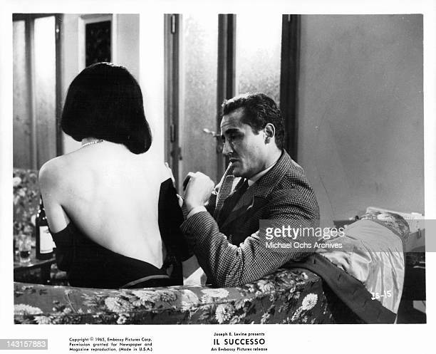 Annie Gorassini and Vittorio Gassman getting close on the sofa together in a scene from the film 'Il Successo' 1965