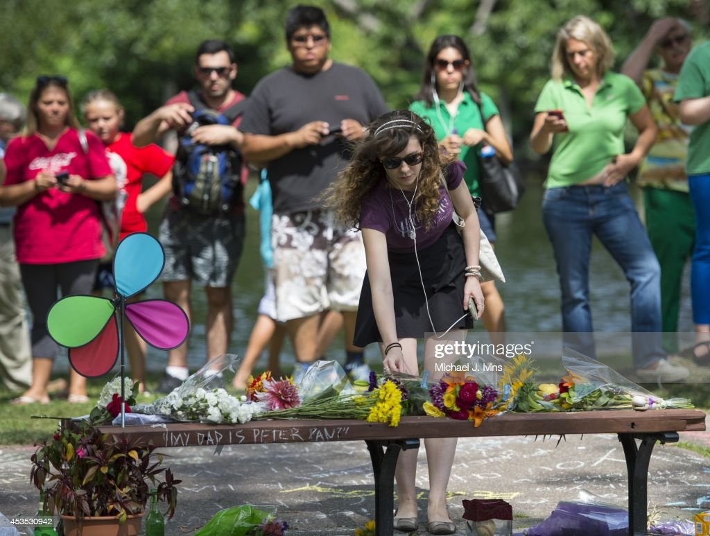 Annie Hochheiser of Cambridge, Massachusetts places flowers onto a fan memorial in honor of Robin Williams on the bench made famous by his movie 'Good Will Hunting' in Boston Public Garden on August 12, 2014 in Boston, Massachusetts. Williams died after hanging himself on August 11, 2014 at his home in Tiburon, California.