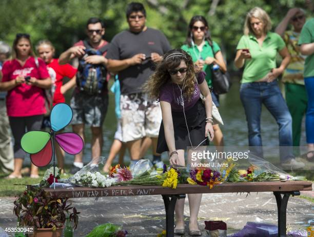 Annie Hochheiser of Cambridge, Massachusetts places flowers onto a fan memorial in honor of Robin Williams on the bench made famous by his movie...