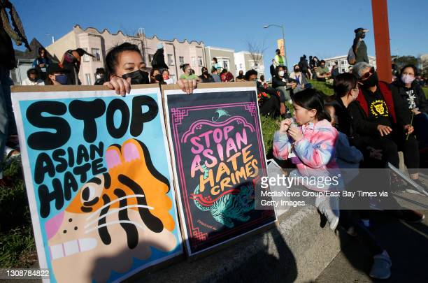 Annie Hong, of Oakland, holds signs during an anti-Asian hate vigil at Chinatown's Madison Park in downtown Oakland, Calif., on Tuesday, March 23,...