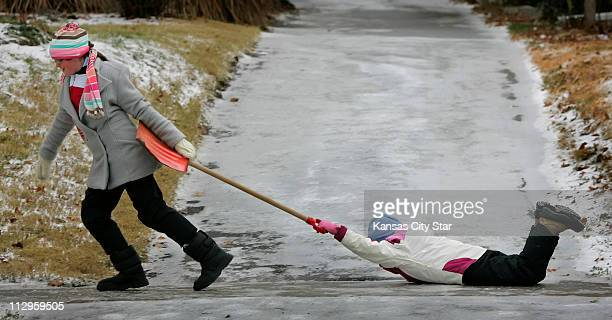 Annie Keel right, receives a pull along an icy sidewalk from Maggie Bowen as Keel held on to Bowen's snow shovel handle as the two ventured out into...