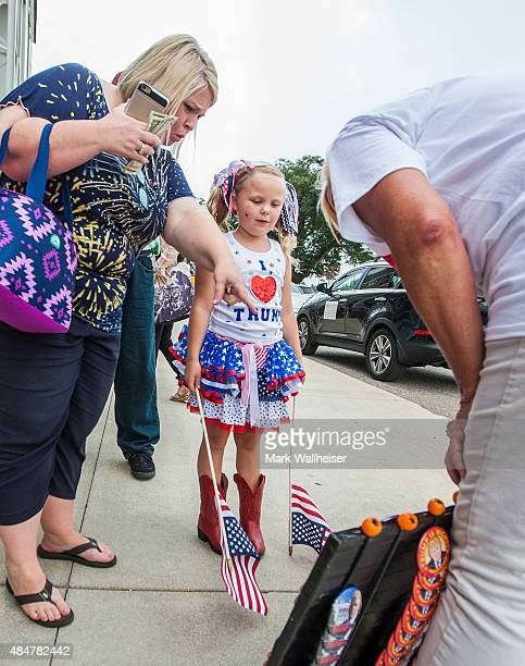 Annie Lamb and her 6 yearold daughter Laci of Lucedale MS pick out a Donald Trump campaign button as they wait in line prior to a Donald Trump...