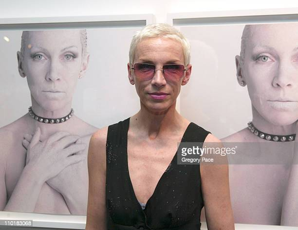 Annie Lennox poses in front of some of her portraits from her Photography Exhibit entitled Bare the self portraits