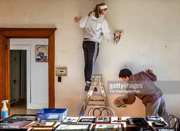 Annie Riley freshman top and Aidan Byrnes sophomore work at cleaning the walls of the Dorothy Day house as Catholic University students fan out into...