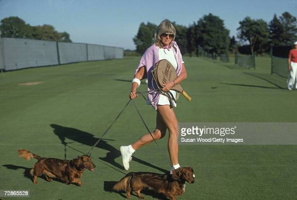 Annie Robertson, in tennis clothes with a pink sweater over her shoulders and a racquet in one hand, walks her two dogs across a grass tennis court...