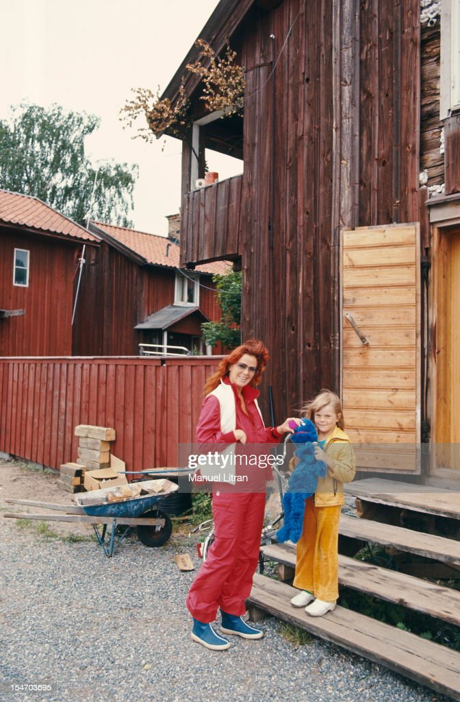 Anni-Frid Lyngstad (Frida called) smiling, posing with his daughter Lisalotte ANDERSSON before a wooden house.