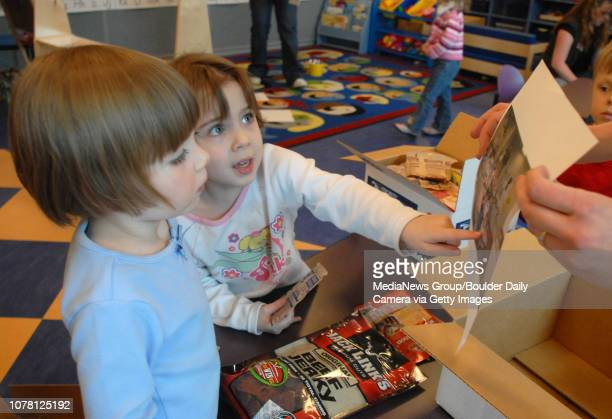 Annika Cunningham left and Lily Carroll look a a picture of their preschool class included with the care packages for soldiers at the Paul Derda...