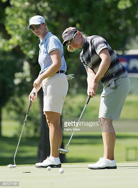 Annika Sorenstam and sister Charlotta Sorenstam of Sweden line up putts on the fifth hole during the practice round of the 2002 US Women's Open at...