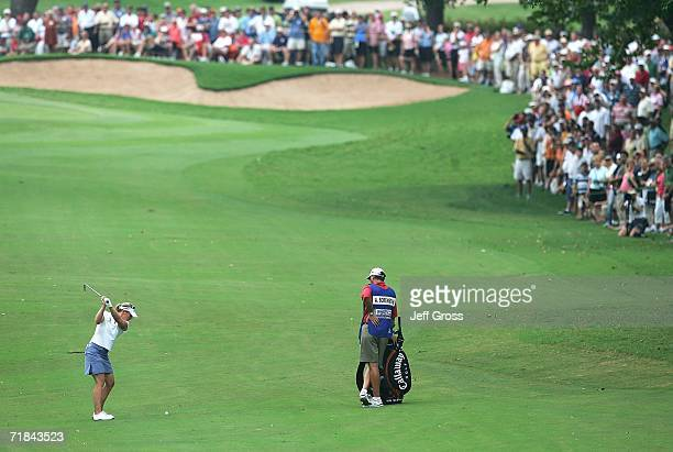 Annika Sorenstam of Sweden hits her second shot from the eighth fairway as her caddie Terry McNamara looks on during the final round of the John Q...