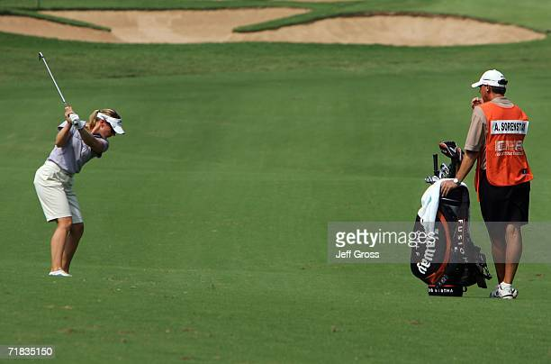 Annika Sorenstam of Sweden hits her second shot from the eleventh fairway as her caddie Terry McNamara looks on during the second round of the John Q...
